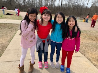 Four girls who are English Learner student stand with arms around each other on the playground